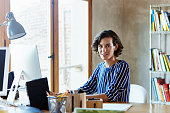 Creative businesswoman sitting at desk in office
