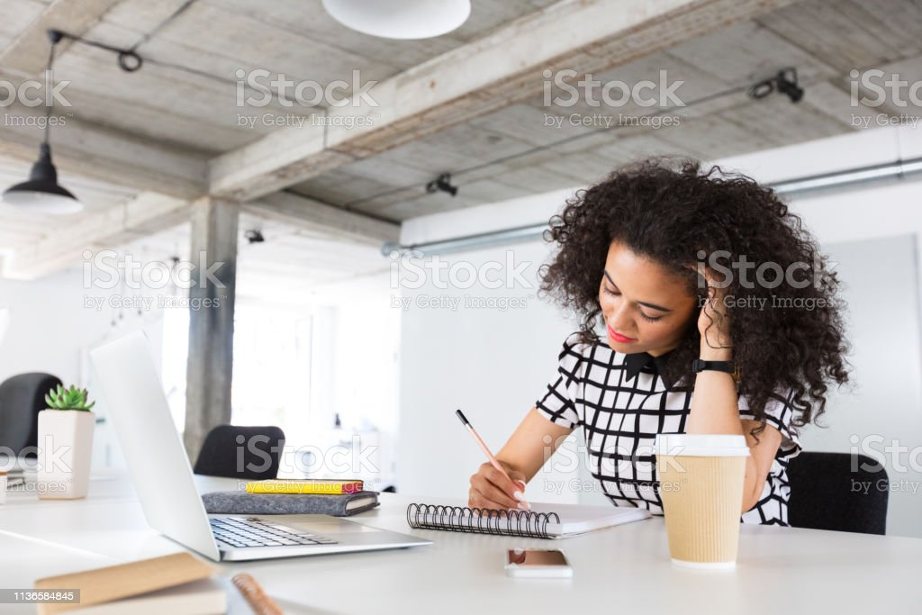Creative businesswoman working at her desk Shot of young business woman sitting at her desk and making a sketch on note pad in office 20-24 Years Stock Photo
