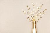 創造的なクリスマスと新年のフラットは、金色のシャンパンボトル、パーティーストリーマー、紙吹雪の星と2020年の数字と構成を置きます。