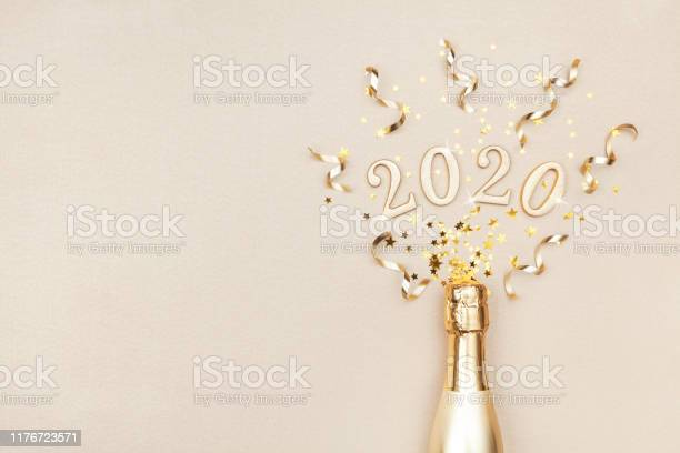 Creative Christmas And New Year Flat Lay Composition With Golden Champagne Bottle Party Streamers Confetti Stars And 2020 Numbers - Fotografias de stock e mais imagens de 2020