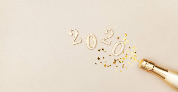 creative christmas and new year greeting card with golden champagne bottle, confetti stars and 2020 numbers. flat lay. banner format. - new years day stock pictures, royalty-free photos & images