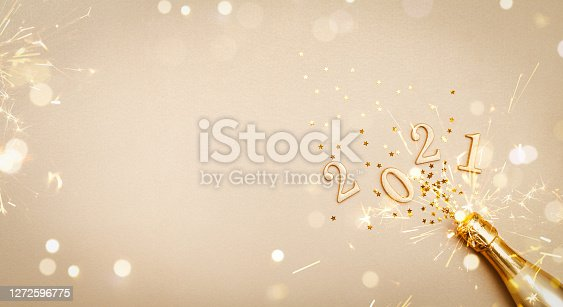 Creative Christmas and New Year greeting card with golden champagne bottle, confetti stars and 2021 numbers. Modern flat lay. Banner format.