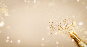 istock Creative Christmas and New Year greeting card with golden champagne bottle, confetti stars and 2021 numbers. Flat lay. Banner format. 1272596775