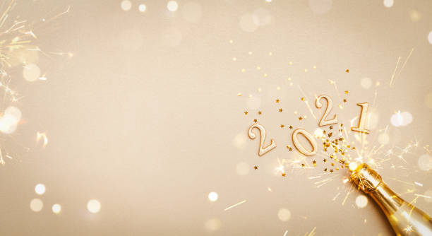 Creative Christmas and New Year greeting card with golden champagne bottle, confetti stars and 2021 numbers. Flat lay. Banner format. Creative Christmas and New Year greeting card with golden champagne bottle, confetti stars and 2021 numbers. Modern flat lay. Banner format. 2021 stock pictures, royalty-free photos & images