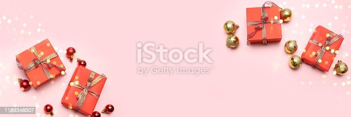 istock Creative christmas background with beautiful gifts boxes, golden shiny ribbons and red balls on pink background with copy space. 1189346507