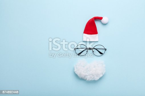 istock Creative christmas composition. Greeting card, invitation or flyer. Santa hat, beard and glasses on blue background top view. 874892448