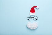 Creative christmas composition. Greeting card, invitation or flyer. Santa hat, beard and glasses on blue background top view. Flat lay. Copy space for text and design.