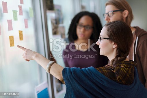 istock Creative colleagues reviewing ideas on wall in studio office 637939370