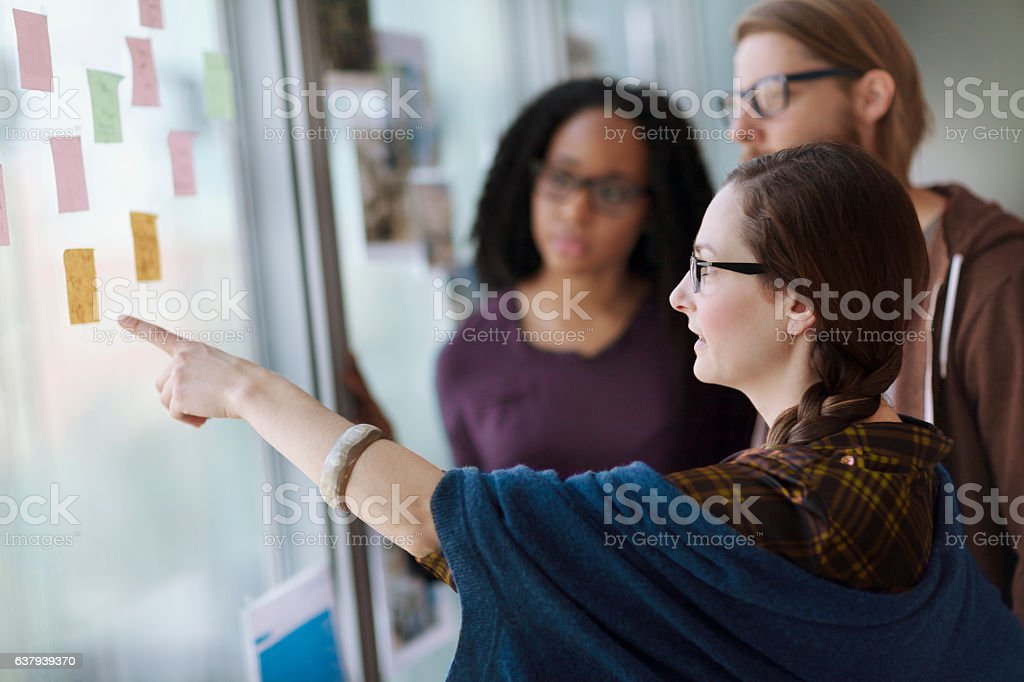 Creative colleagues reviewing ideas on wall in studio office stock photo