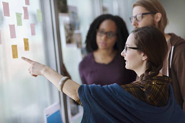 creative colleagues reviewing ideas on wall in studio office - scoprire nuovi terreni foto e immagini stock