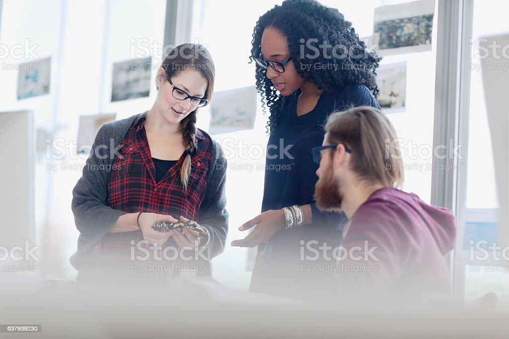 Creative colleagues reviewing product samples in studio office stock photo