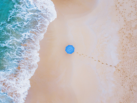 istock creative colorful shot of beach umbrella near ocean wave from above 1155162406