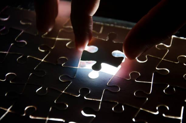 Un créateur complète le puzzle noir mettant la dernière pièce manquante lumière bleue - Photo