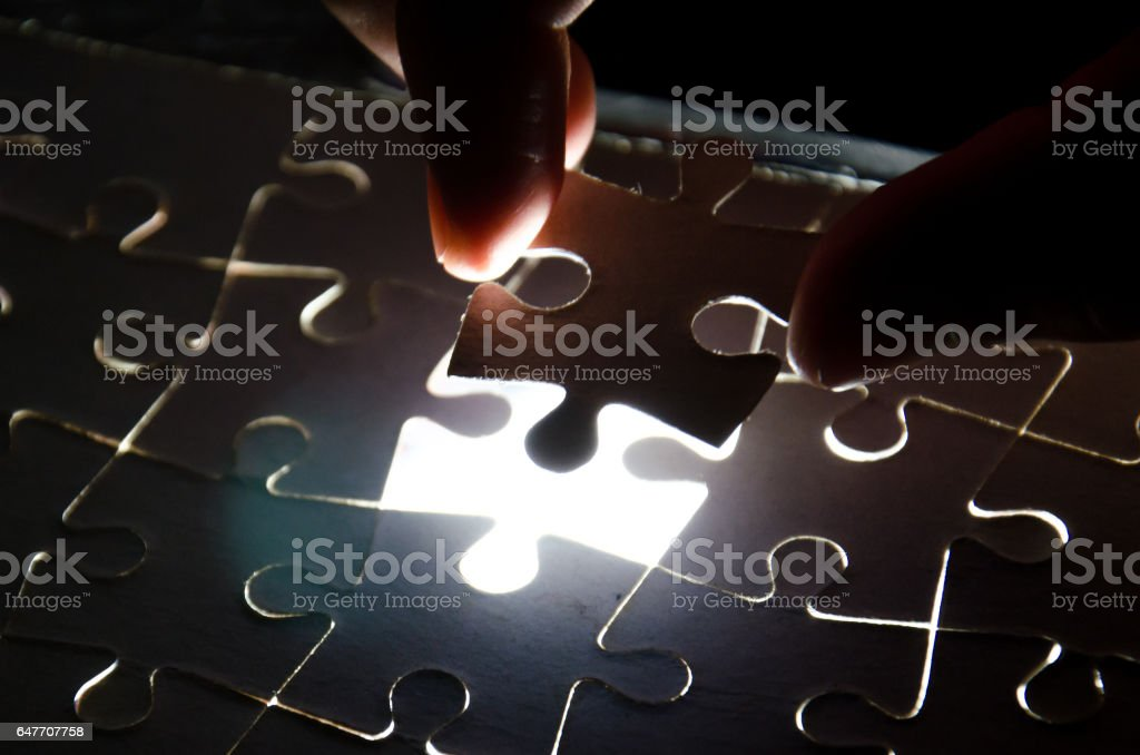 A creative completes the black puzzle putting the last missing piece blue light stock photo