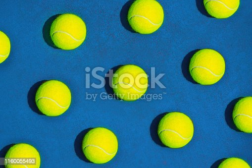 1153628111 istock photo Creative composition made with tennis ball on blue background. 1160055493