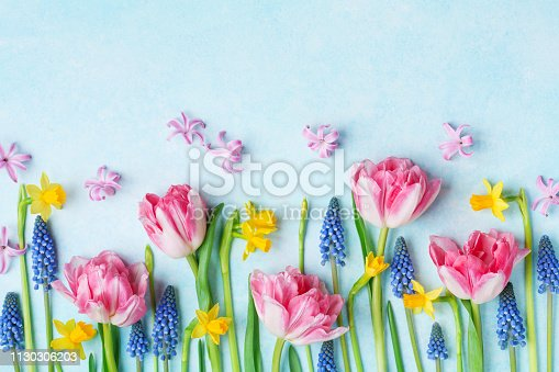 Creative composition of beautiful spring flowers on pastel table top view. Greeting card for International Women or Mother Day. Flat lay.