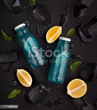 Creative composition of blue detox water with fresh lemon on black background with ice cubes