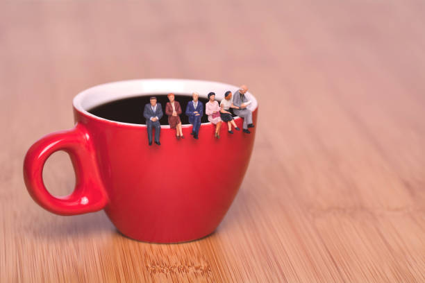 creative concept about drinking coffee and waiting. miniature people sit on the edge of a cup of coffee tea coffee break. red cup on a wooden background. - маленький стоковые фото и изображения