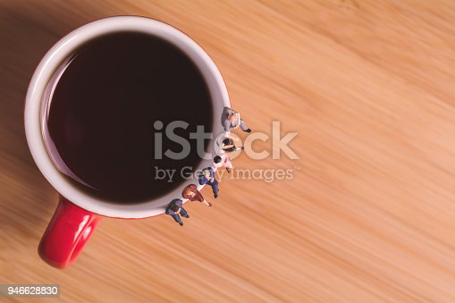 istock Creative concept about drinking coffee and waiting. Miniature people sit on cup 946628830