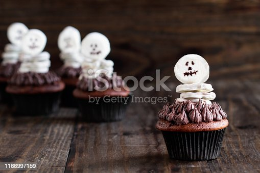 Creative concept of skeleton made from white chocolate pretzels and marshmallows over a dark chocolate cupcake. Selective focus on one in front with blurred background.