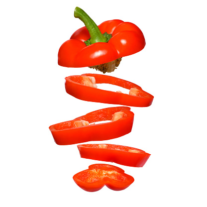 Creative concept with flying red paprika. Sliced floating pepper isolated. Levity vegetable. Capsicum