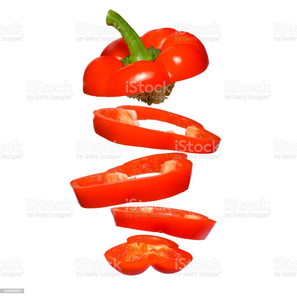Creative concept with flying red paprika. Sliced floating pepper isolated. stock photo