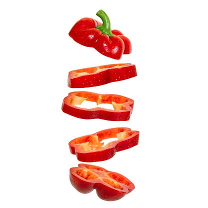 Creative concept with flying red paprika. Sliced floating pepper. Levity capsicum vegetable isolated on white background