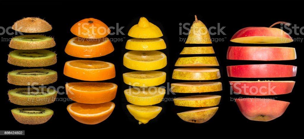 Conceito criativo com comida. Conjunto de frutas fatiadas isoladas no fundo preto. - foto de acervo