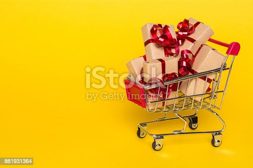 istock Creative concept with shopping trolley with gifts on a yellow background 881931364