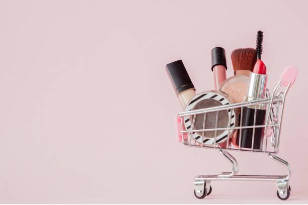 創意的概念與購物車化妝在粉紅色的背景。香水、海綿、刷子、睫毛膏、鉛筆、指甲檔、眼影、草影、嬰兒籃內的唇彩、複印空間 - 美容品 個照片及圖片檔