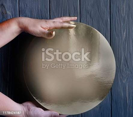 Creative conceptual photo of hands that hold a round golden tray on a gray wooden background. Frame for text
