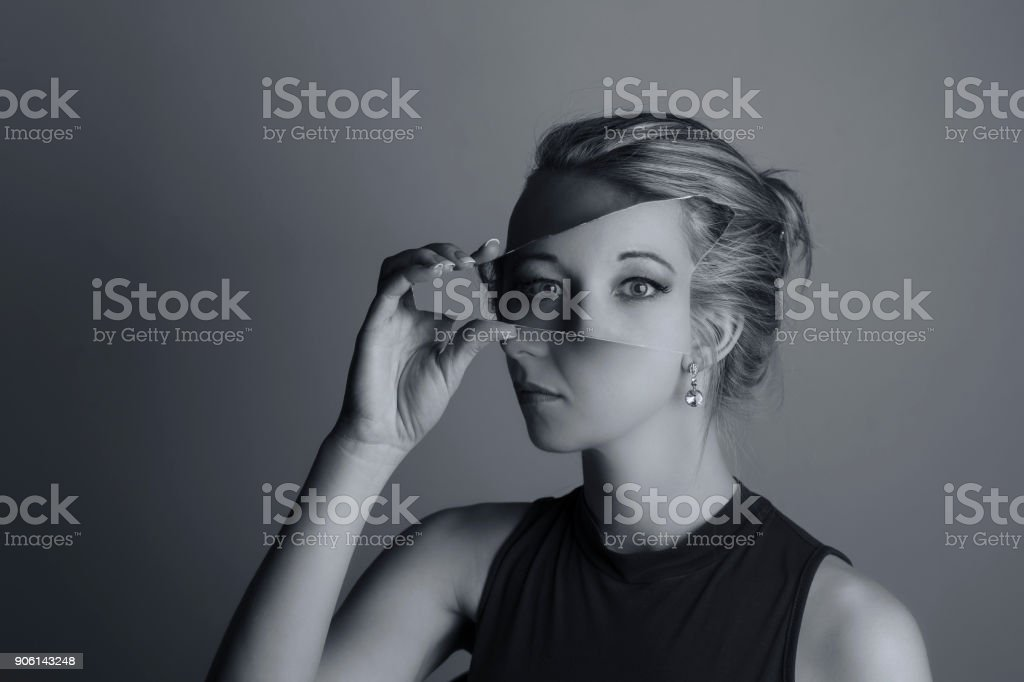 Creative conversion of a woman holding a shard of broken mirror and eyes from another exposure artistic conversion stock photo