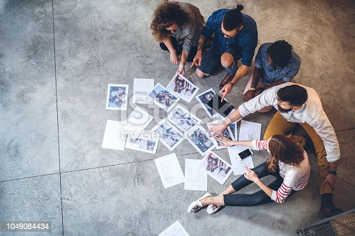 Cheerful Young Colleagues, Designers, Choosing Photographs And Designs While Sitting On Office Floor