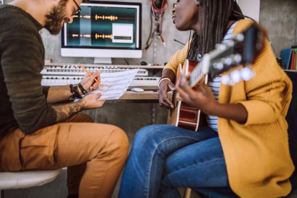 kreatives paar, das im studio songs schreibt - musiknoten tattoos stock-fotos und bilder