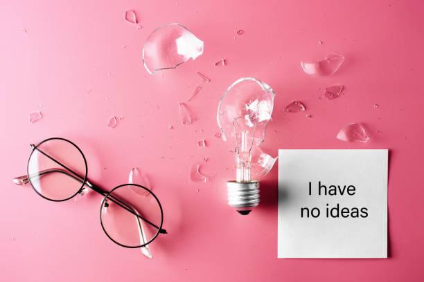 Kreative Krise. Gläser und gebrochene Glühbirne auf rosa Hintergrund. Das Konzept des Mangels an Ideen und Inspiration. – Foto
