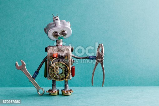 istock Creative design electrician robot with hand wrench pliers. Funny toy mechanic character lamp bulb eyes head, electric wires, capacitors vintage resistors. Green paper background copy text 670967580