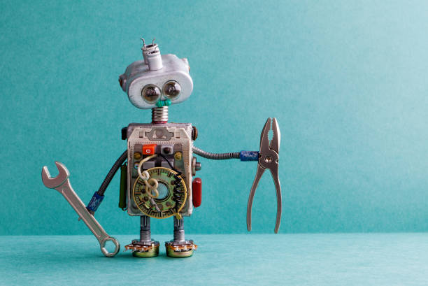 Creative design electrician robot with hand wrench pliers. Funny toy mechanic character lamp bulb eyes head, electric wires, capacitors vintage resistors. Green paper background copy text stock photo