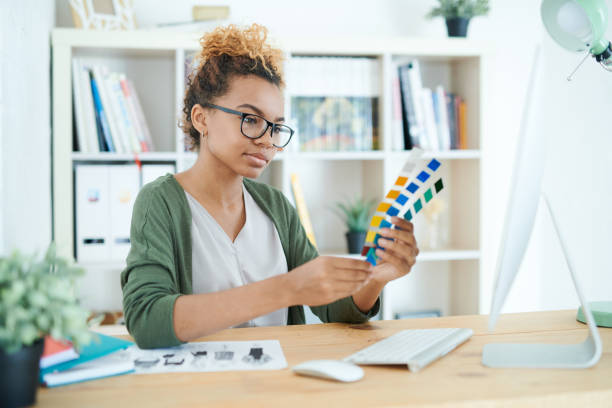 Creative Designer at Work Portrait of young African-American woman holding swatches while choosing color scheme  in design agency interior designer stock pictures, royalty-free photos & images