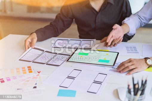 995213208 istock photo Creative designer choosing color samples for mobile responsive website development with UI/UX. Developing wireframe sketch layout design mockup on smartphone screen. 1130646279