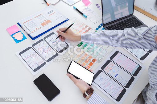 1182469817istockphoto Creative designer hands sketching of screens for mobile responsive website development with UI/UX. Developing wireframe sketch layout design mockup on smartphone screen. 1056993168