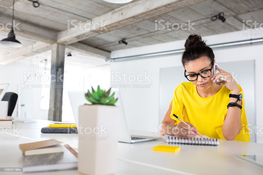 Creative designer working at her desk Designer drawing sketch and talking on cell phone. Female creative professional making a phone call to the client while preparing new design. 20-24 Years Stock Photo