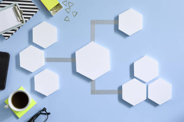 kreative schreibtisch mit weißen mock-up sechseck formen des diagramms, büroartikel, notebooks und tasse kaffee. konzept der modernen herangehensweise an management-projekt. blauem hintergrund schreibtisch. - unterrichtsplanung vorlagen stock-fotos und bilder