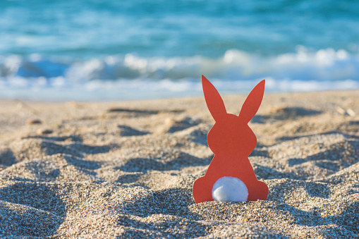 Creative easter photo of red paper bunny on the sand on the beach at sunset. Concept of Easter celebrations in tropical countries.