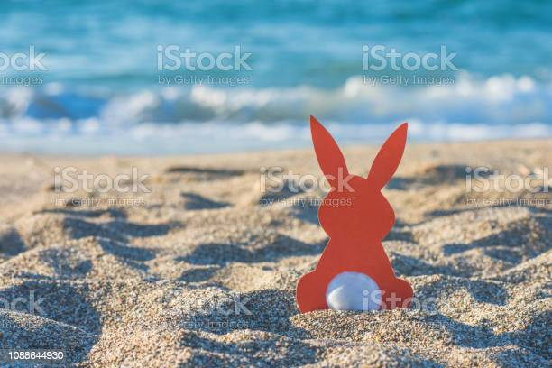 Creative easter photo of red paper bunny on the sand on the beach at picture id1088644930?b=1&k=6&m=1088644930&s=612x612&h=bqugawl05aa70vuyc vnbf2jjwof21nb nfuw8cu1v0=
