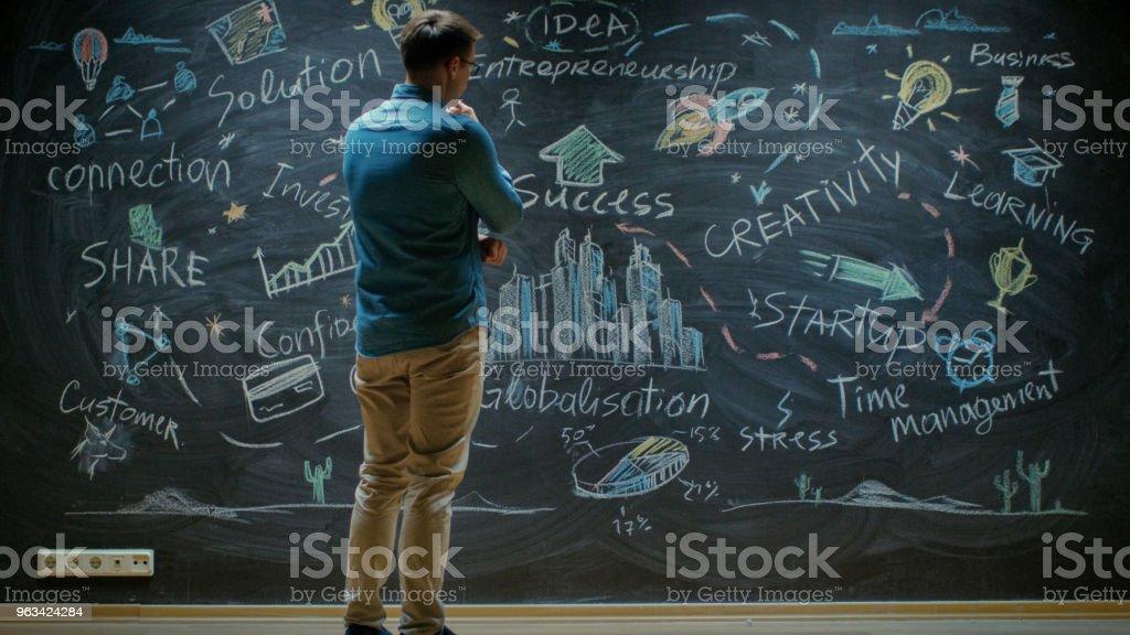Créative Entrepreneur se dresse avant Blackboard ressemble au tableau noir avec les mots inspirants et penser à elle. - Photo de A la mode libre de droits