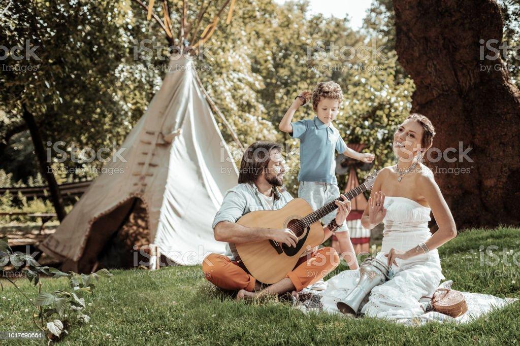 Família criativa, tocando instrumentos musicais perto da tenda - foto de acervo