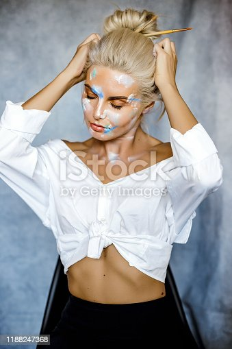 Creative fashion beauty portrait of beautiful young blonde woman with hairstyle. Model girl with professional make-up and body art on gray background.