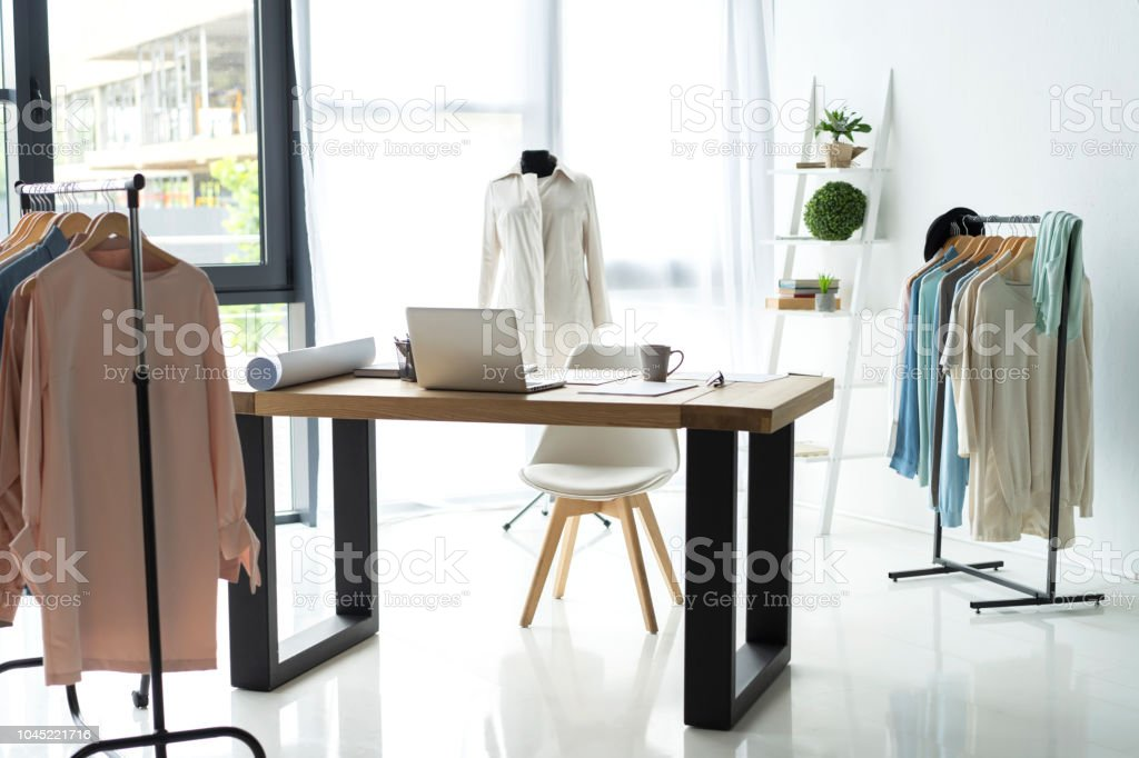 Creative fashion designer desk or workplace with sewing equipment, fabrics, templates, modern stylist inspirational office, dressmaker atelier with mannequin and clothes on hangers, couturier showroom stock photo