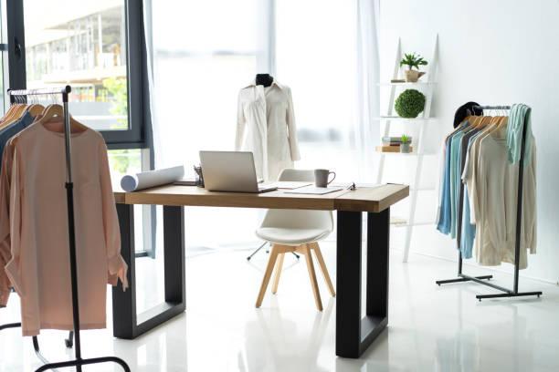 kreative mode-designer schreibtisch oder arbeitsplatz mit näheinrichtung, stoffe, vorlagen, moderne stylist inspirierende büro, schneiderin atelier mit puppe und kleidung auf kleiderbügeln, couturier showroom - exklusive mode stock-fotos und bilder