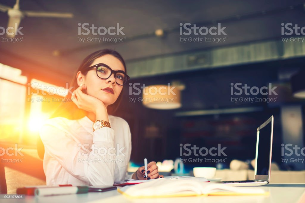 Creative female journalist concentrated on writing press release waiting for inspiration  assemble together news stories that will interest their audience working in coworking office using laptop stock photo